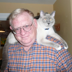 Man with cat on his shoulders.